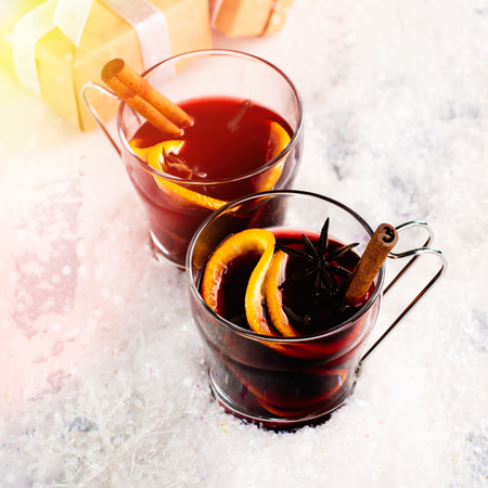 Homemade christmas mulled wine or hot tea with cinnamon, anise and oranges over white background. Toned image. Selective focus Stock Photo