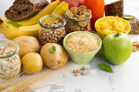 Assortiment producten die rijk zijn aan complexe koolhydraten. Gezond eten op witte steenachtergrond. Ruimte voor tekst
