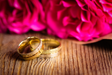 Wedding rings and roses bouquet. Valentines day card. shallow depth of field. Toned image Stock Photo