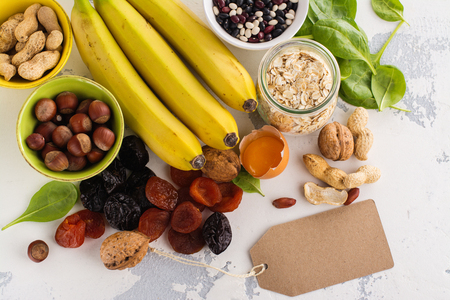 Products rich of potassium (K). Bananas, spinach, nuts, grains, dried fruits overs stone table. Space for text