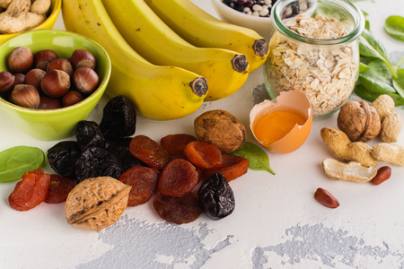 Products rich of potassium (K). Bananas, spinach, nuts, grains, dried fruits overs stone table. Space for text Stock Photo - 77407958
