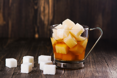 glycemic: Excessive portion of sugar in mug with tea. Stock Photo