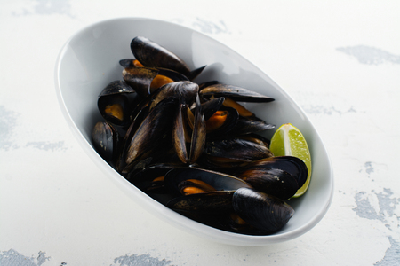 Mussels in shells, tasty seafood rich of iodine in white bowl Banco de Imagens