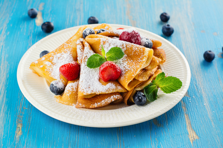 maslenitsa: Crepes with jam, berries and sugar powder.