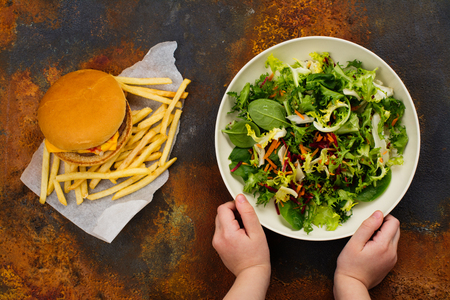 Child making choice between healthy salad and fast food. Choosing healthy meal instead of burger. Archivio Fotografico