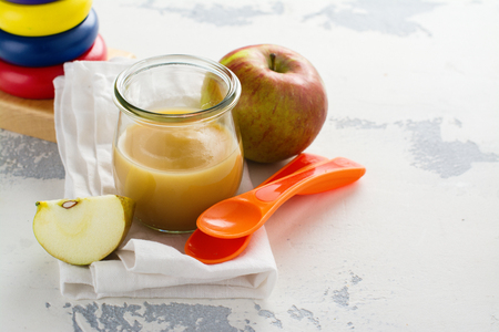Assortment of baby food in glass jars. Homemade vegetable and fruit puree with ingredients on white background. Space for text