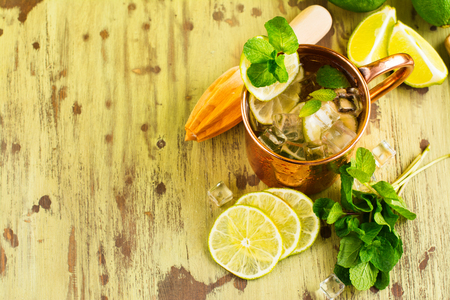 Mojito cocktail with mint, lime in copper mug. Summer drink on wooden background