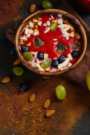 Breakfast strawberry smoothie bowl with berries and nuts. Fresh summer meal. Space for text Stock Photo