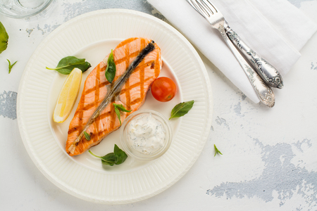 Grilled salmon steak with tartar sauce on white plate. Space for text
