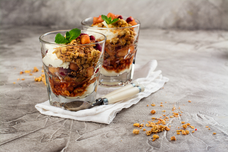 Layered dessert with granola, apple and red bilberry compote, cream