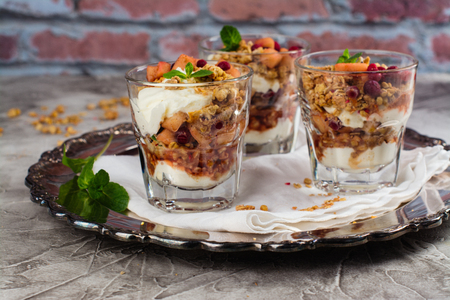 trifle: Layered dessert with granola, apple and red bilberry compote, cream
