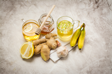 rheum: Selection of food against flu. Natural product for excellent immunity - herbal tea, lemon, ginger, honey, bananas and broth soup. Space for text