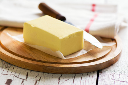 Butter block on wooden board. Baking or cooking concept Foto de archivo