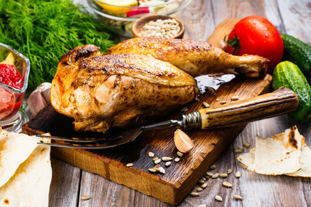 Roasted chicken with pita bread, tomato sauce and fresh raw vegetables on wooden table Stock Photo
