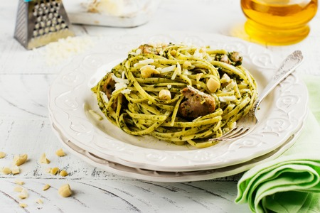 Homemade pasta spaghetti with pesto sauce, chicken and cashew nuts. Space for text