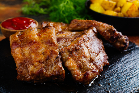 BBQ pork ribs and golden potato wedges. Copy space