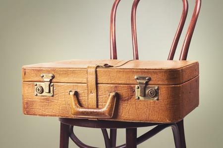 壁に沿って古い椅子立ってビンテージ革のスーツケース。トーンのイメージ。テキストのためのスペース