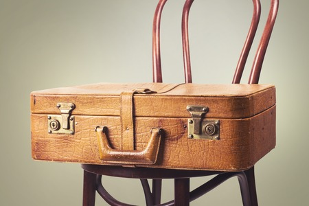 Vintage leather suitcase on an old chair standing along the wall. Toned image. Space for text