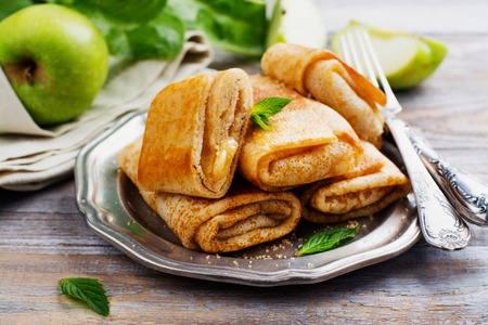 Crepes with apples, lemon and cinnamon on wooden table. Space for text Stock Photo