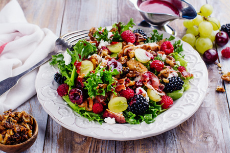 Delicious summer salad with mix of berries, nuts, feta chees, bacon and raspberry sauce on vintage background. Space for text Reklamní fotografie - 84886395