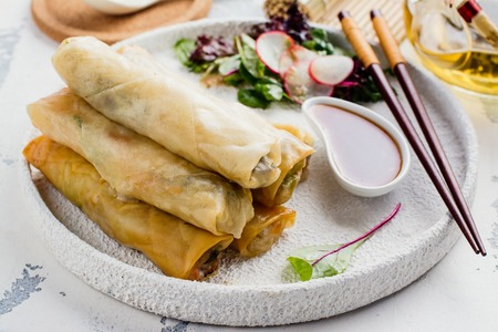 Fried spring rolls with vegetables, duck meat and noodle on white stone table. Copy space. Top view Stock Photo