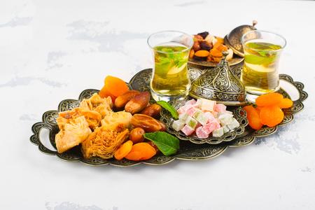 baklava: Ramadan Kareem holiday table with dry fruits, nuts, dates, baklava. Eastern abundance. Copy space Stock Photo