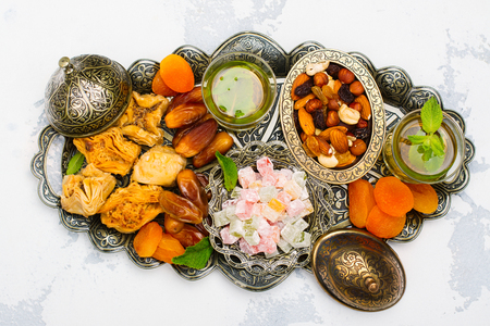 Ramadan Kareem holiday table with dry fruits, nuts, dates, baklava. Eastern abundance. Copy space Stock Photo