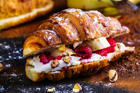 French croissants with cream cheese and raspberry, cinnamon and almond nuts. Copy space