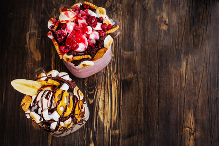 pretzel: Vanilla and raspberry extreme milkshakes with pretzels, popcorn, small marshmallows, cookies and berries on dark wooden background. Copy space Stock Photo