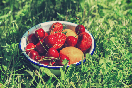 flat earth: Bowl of fresh summer berries and fruits. Delicious lunch or picnic concept. Toned image. Flat lay style