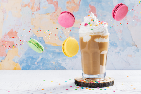 Crazy coffee cocktail and macaroons on wooden table
