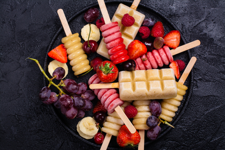 popsicles: Homemade bright fruit and berry popsicles on stone table Foto de archivo