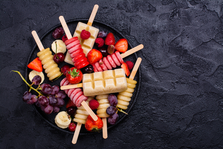 Homemade bright fruit and berry popsicles on stone table Stock Photo