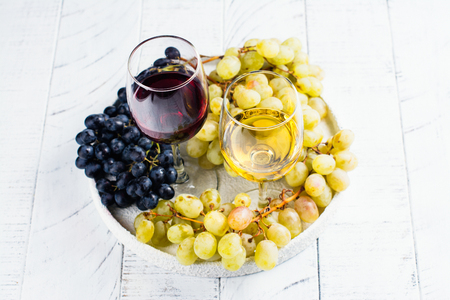 Red and white wine in glasses with grapes on white background. Assortment of autumn harvest beverages. Copy space