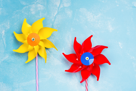 Colorful paper windmill toys on blue stone background. Summer concept. Copy space