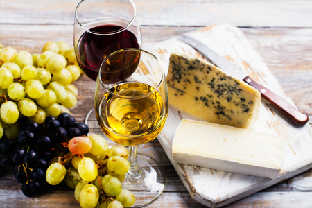 Red and white wine in glasses and assorted cheese plate with grapes Stock Photo