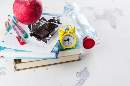 School exams concept. Books, apple, chocolate bar over white table. Space for text Stock Photo