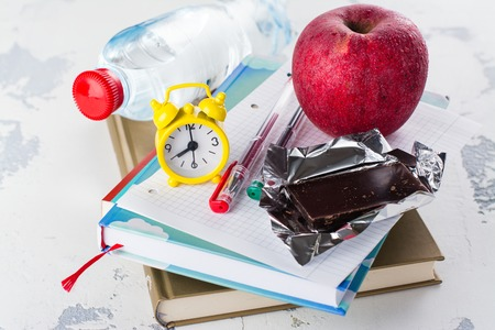 School exams concept. Books, apple, chocolate bar over white table. Space for text Imagens