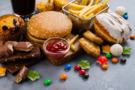 Assortment of unhealthy products thats bad for figure, skin, heart and teeth. Fast carbohydrates food. Space for text