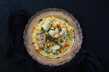 Couscous with fish and vegetables on sto
