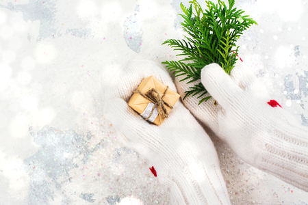 Women is holding a small gift box in hands worn in white knitted mittens. Winter holidays background. Top view Stock Photo