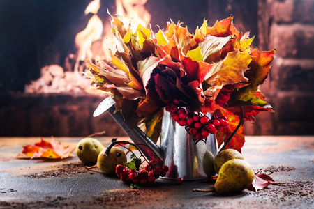 Watering can with autumn leaves and ripe pears near fireplace. Thanksgiving day or fall concept. Copy space Archivio Fotografico