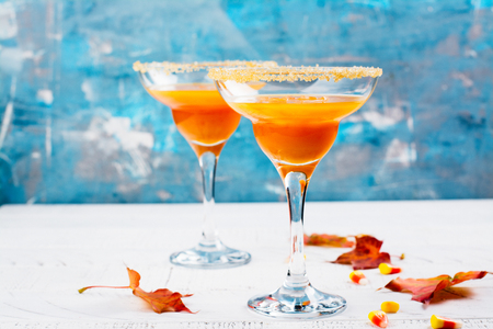 Autumn pumpkin martini cocktail with halloween decor on wooden table. Copy space