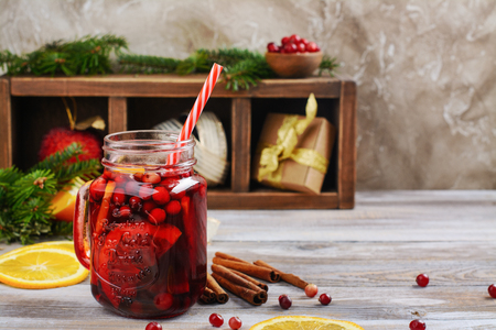 Cranberry and orange mulled wine with ingredients on Christmas decorated background. Copy space