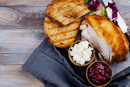 Homemade leftover thanksgiving day sandwich with turkey, cranberry sauce, feta cheese and vegetables on wooden table. Top view. Copy space Stock Photo
