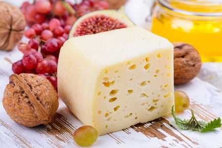 Yellow cheese brick with spices and snacks on white wooden board