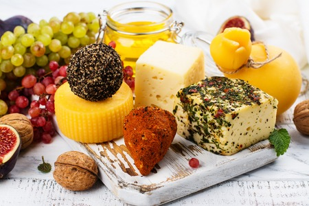 Assortment of farm cheese with supplemental snacks, fruits and nuts on white wooden table