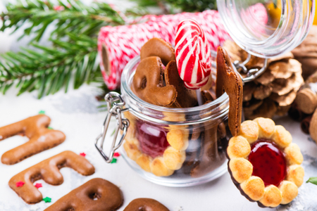 Christmas cookies on festive decorated background. Letters Merry Christmas and jar with cookies and candies