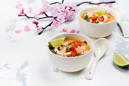 Traditional Tom Yum soup with blooming sakura branch on white stone table Stock Photo