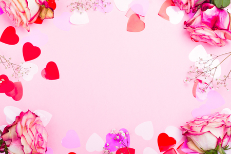 Beautiful pink rose, decorative confetti hearts and pink ribbon on pink Valentines day background Foto de archivo